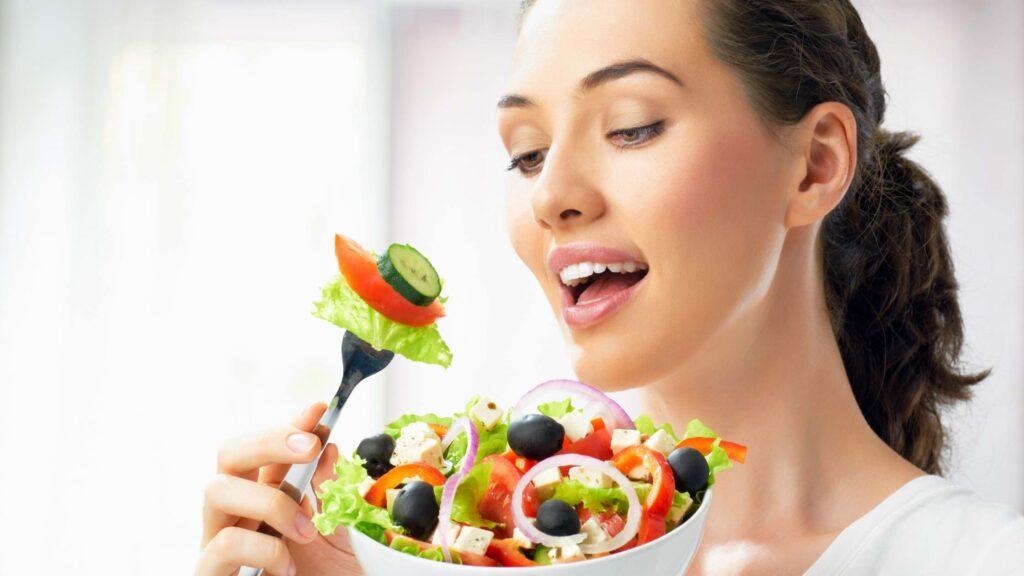 Chica come verdura para su pie diabético